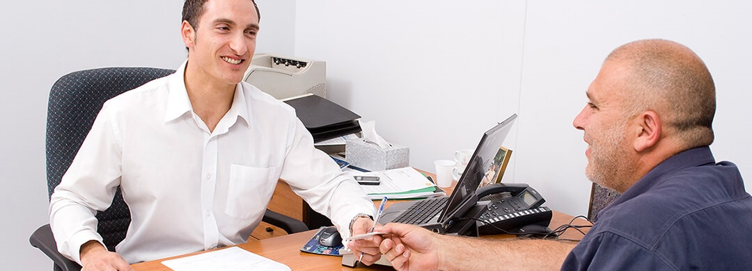 A CMI Hino employee helping a customer at a desk